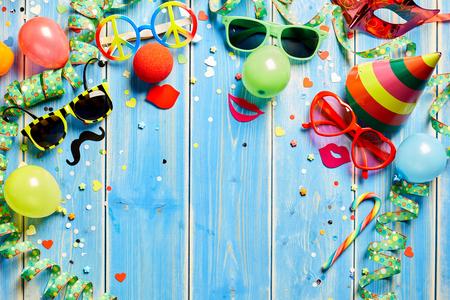 Kleurrijk carnaval kader van heldere foto booth accessoires, streamers, party hoed en confetti op rustiek blauwe houten planken met centrale kopie ruimte Stockfoto
