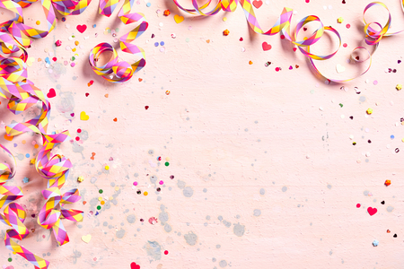 Delicate pink party background with colorful streamers for celebrating a carnival forming a border around copy space with scattered confetti