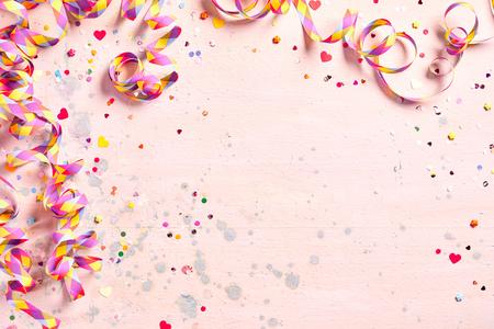 Gevoelige roze partijachtergrond met kleurrijke wimpels voor het vieren van Carnaval die een grens vormen rond exemplaarruimte met verspreide confettien