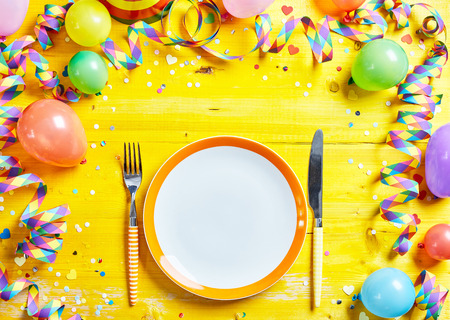 fasching: Bright yellow place setting for the carnival season with coiled streamers, party balloons and confetti around a clean empty plate with knife and fork viewed from above
