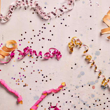 fasching: Square party or carnival background with scattered colorful confetti and coiled streamers on light pink textured wood Stock Photo