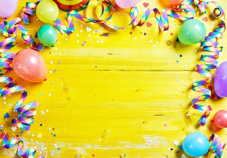 Carnaval coloré brillant ou cadre de partie de ballons, des banderoles et des confettis sur une table en bois jaune rustique avec un espace central de copie pour votre salutation, invitation ou publicité