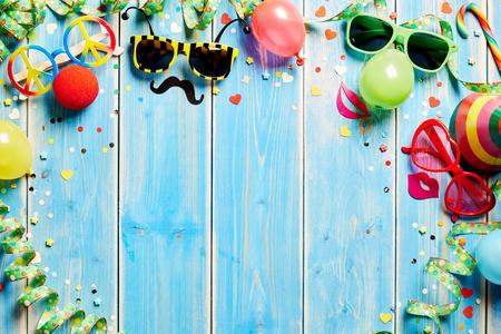Carnaval frame met kleurrijk kostuum accessoires in de vorm van plezier vormige zonnebril, een feest hoed en streamers opgerold op een blauwe houten achtergrond met een kopie ruimte Stockfoto