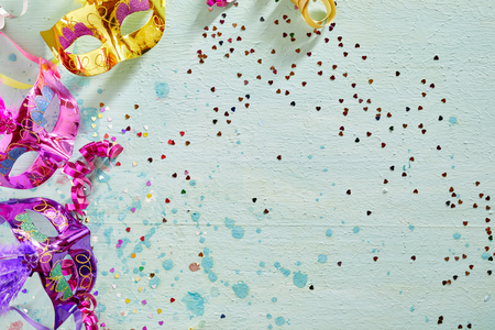 twirled: Brightly colored carnival or Mardi Gras border with metallic foil eye masks decorated with feathers and twirled streamers on a light blue wood background with scattered confetti and copy space