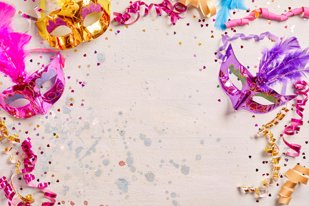 twirled: Mardi Gras or carnival frame with brightly colored metallic foil masks with feather decoration and twirled streamers on a pale pink background with copy space