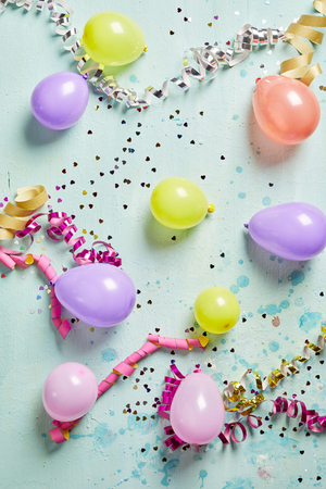 twirled: Colorful party background with twirled streamers, confetti and balloons scattered across a blue background