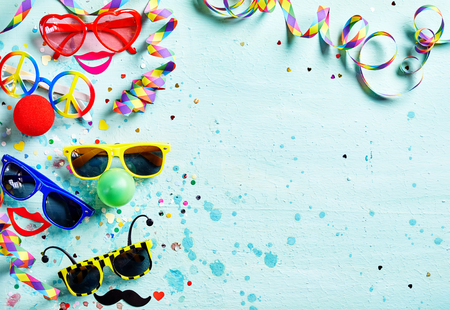 fasching: Colorful fun carnival or photo booth accessories with assorted shaped glasses and noses, bright red lips, confetti and streamers forming a side border on light blue textured wood with copy space Stock Photo
