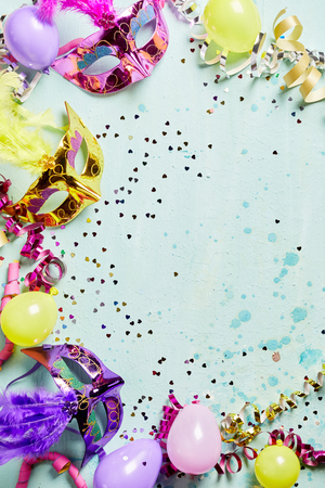Carnival or Mardi Gras masks in a colorful border with streamers and party balloons around a textured light blue copy space for your advertising or greeting Imagens - 69278496