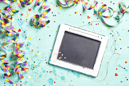 twirled: Vintage slate carnival or party background with multicored twirled streamers and scattered confetti, copy space on the chalkboard viewed from above