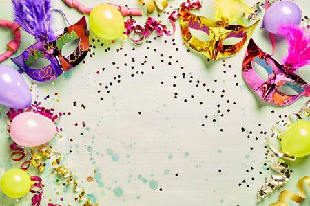 カラフルな金属箔カーニバル マスクとパーティ風船吹流しと紙吹雪中央光緑コピー スペースの周りフレームを形成 写真素材