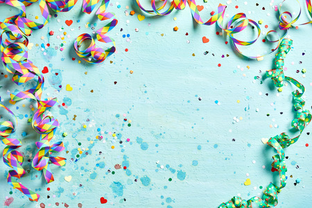 Festive party or carnival border of coiled streamers and confetti on a light blue green wood background with copy space 스톡 콘텐츠
