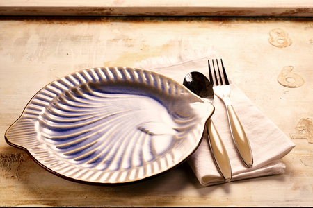 Empty plate with cutlery on wooden background for advertising concepts