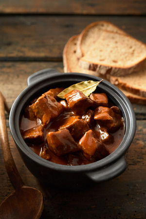 Bread and goulash on vintage plate in a rustic rural pot with traditional german food