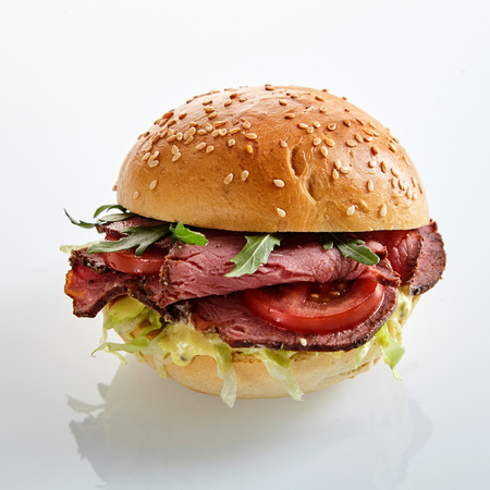 Delicious roast beef burger with salad trimmings and rocket on a fresh sesame bun on a reflective white surface 写真素材