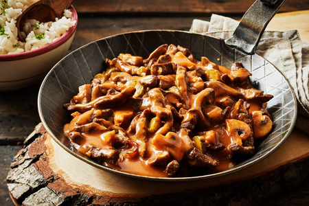 Metal skillet filled with rich beef stroganoff in a thick spicy gravy with mushrooms served with a side dish of rice Stock fotó