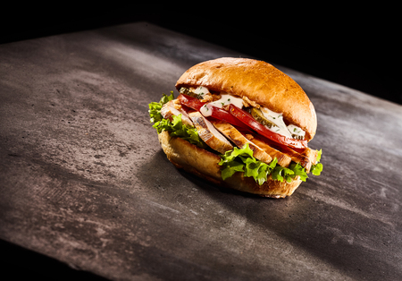 Studio shot of burger with chicken on metal or stone dark surface and black background