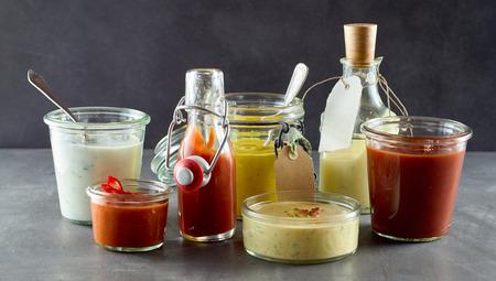 Selectie van diverse sauzen en dressings in verschillende containers om te dienen met afhaalmaaltijden of gebarbecued voedsel, waaronder, saus, chili, ketchup, mayonaise, mosterd, en hartige olie Stockfoto