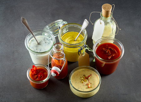 Assortment of dressings, sauces and condiments with chili, ketchup, catsup, mustard, oil and mayonnaise , in various containers viewed from above in a catering and takeaway concept