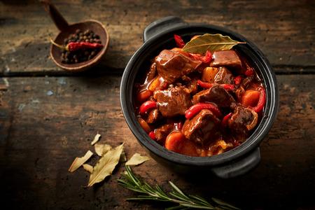 装飾食品いけばなと古代の黒い背景にハンガリーのグーラッシュのキャセロールのオーバー ヘッド ビュー