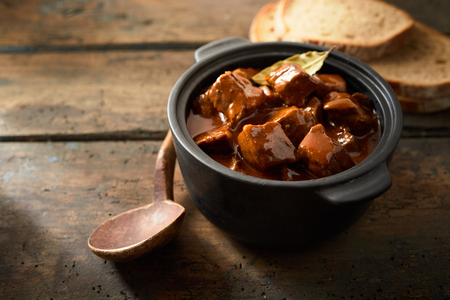 Seasoned Hungarian beef goulash in a rich gravy with bay leaves and paprika served on a rustic wood table in a crock or casserole dish with sliced bread, copy space to the side