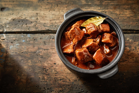 Whole pot of goulash in an aerial view with copy space on brown wooden table Фото со стока