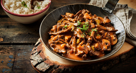 Food banner of meat cut into strips. Pan with goulash stroganoff meal on rustic wooden plate