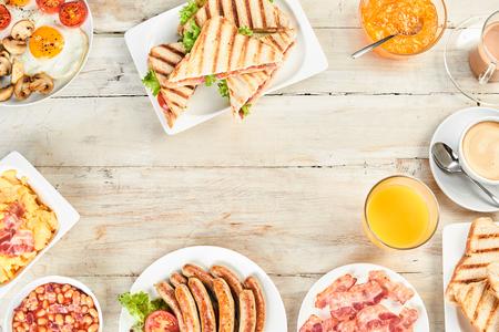 Diverse kommen en schotels van Engels ontbijt met bonen, ham en eieren, jus d'orange en diverse soorten traditionele Engelse keuken in bovenaanzicht Stockfoto