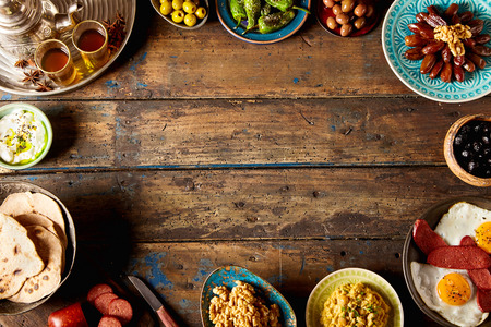 moroccan cuisine: Overhead view of a oriental breakfast border on vintage old wood with copy space. Stock Photo