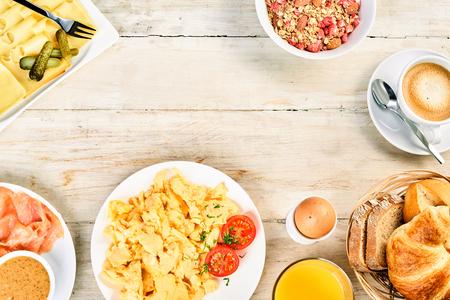 スクランブルエッグの朝食国際食品フレーム、無作法な木に中央コピー スペースの周りのハム、ロール、クロワッサン、シリアル、コーヒー、オレ 写真素材