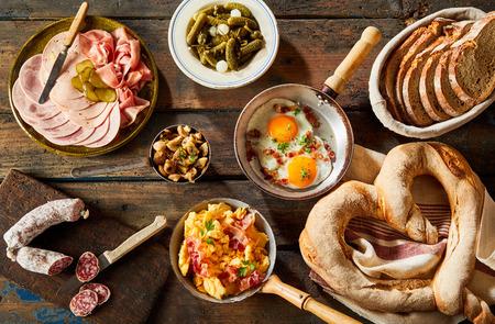 arabian food: Heart shaped bavarian pretzel on napkin beside dish of sliced meats and pot of savory eggs