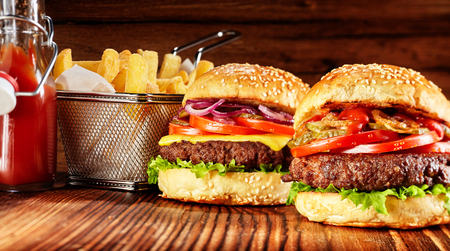 Two tasty burgers with basket of Frencg fries and red sauce on wooden background