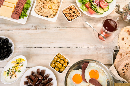 carnes y verduras: Overhead view of oriental breakfast with naan, turkish Suck meat sunny side up eggs, dates, hummus and tasty arabic tea. On rustic white wooden background with copy space Foto de archivo