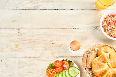 Corner border of international breakfast food with cucumber salad, fresh bread and croissants, a boiled egg and plate of cereal on rustic white wood background with copy space