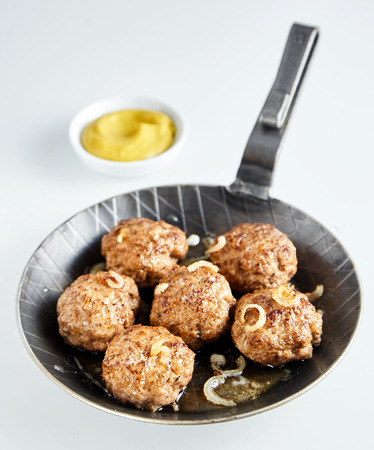 seasoned: Pan fried tasty German frikadelle, or meatballs made with ground beef and veal seasoned with onion, served with mustard in an old skillet over a light grey background