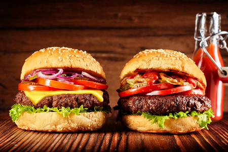 Side view of two freshly made burgers, one with cheese, with red sauce and fries on rustic wooden background