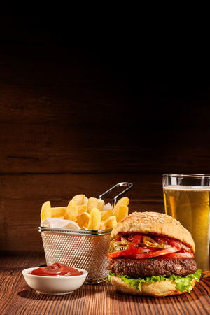 Freshly made beef burger with basket of fries, bowl of ketchup and pint of lager on wooden table, vertical images with copy space