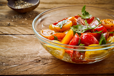 Delicious summer salad with assorted tomatoes spiced with various seasonings in a glass bowl on an old vintage table Stock Photo