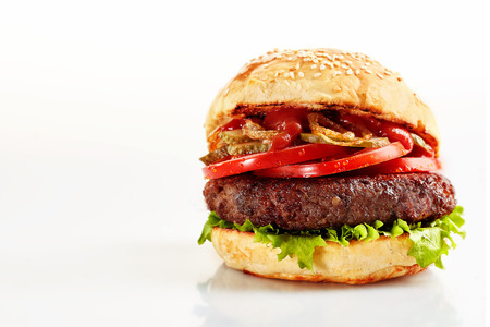 Freshly made beef burger with tomatoes and lettuce on white background with copy space Stock Photo
