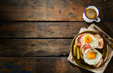 Savory traditional german cuisine with eggs cooked sunny side up on homemade bread with sliced ham