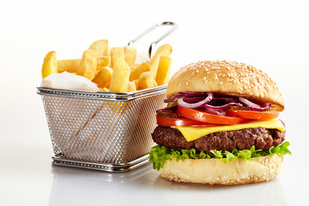 Freshly made cheeseburger with basket of French fries on white background