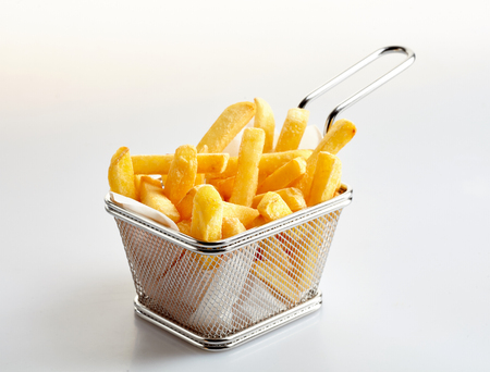 Canestro delle patate fritte appena fatte sulla priorità bassa bianca dello studio
