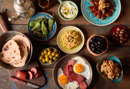 Obenliegende Szene des rustikalen arabischen Frühstücks. Verschiedene Bestandteile des arabischen Frühstücks auf einem alten Vintagen Hintergrundplatte.