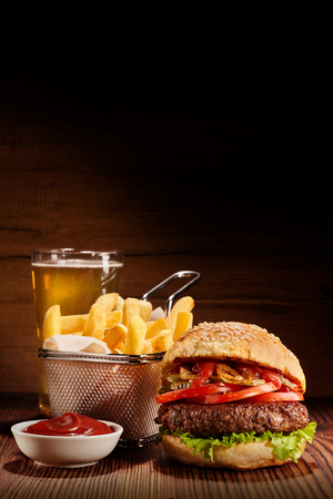 Burger with fries and pint of lagerFreshly made beef burger with basket of fries, bowl of ketchup and pint of lager on wooden table, vertical images with copy space Banco de Imagens