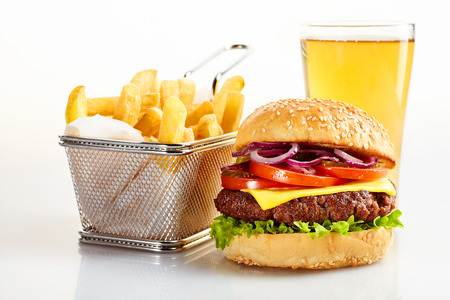 Tasty burger meal with with basket of fries and pint of beer, white background