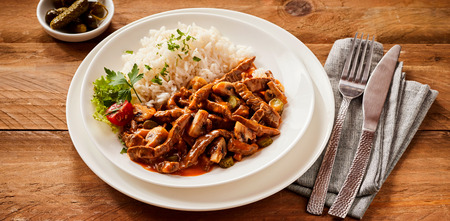 Spicy beef stroganoff with hot chili and gherkin served with rice garnished with fresh herbs on a rustic wood table with cutlery and napkin Stok Fotoğraf