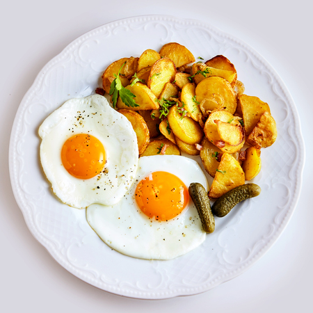 Crisp fried potato slices with two fried eggs seasoned with pepper and garnished with pickled cucumber, overhead view on white