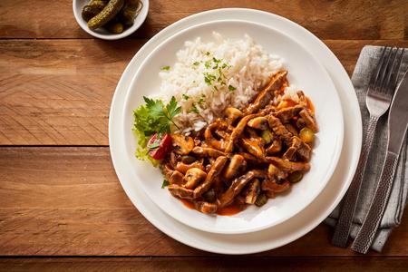 Heerlijke ragout met ingelegde komkommer gekruid met pittige chili pepers en geserveerd in een witte schotel op een rustieke houten tafel van bovenaf gezien