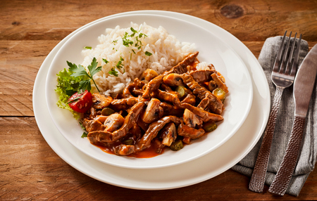 Spicy beef stroganoff served with fluffy white rice seasoned with fresh herbs at a rustic restaurant, high angle view Stock Photo