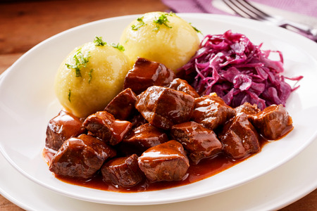 Chunky beef stew with savory sauce beside potato topped with herbs and purple cabbage