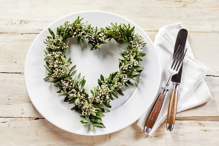 Table setting decorated with green and white wreath in shape of heart over white dish and cutlery set on napkin. Old wooden table surface